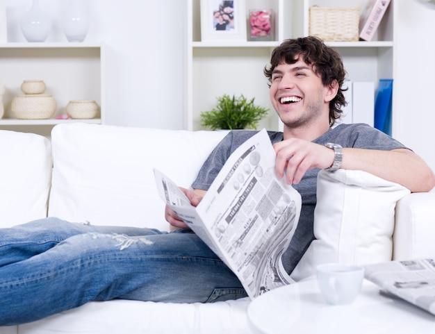Homem bonito feliz rindo em roupas casuais deitado no sofá com o jornal - dentro de casa