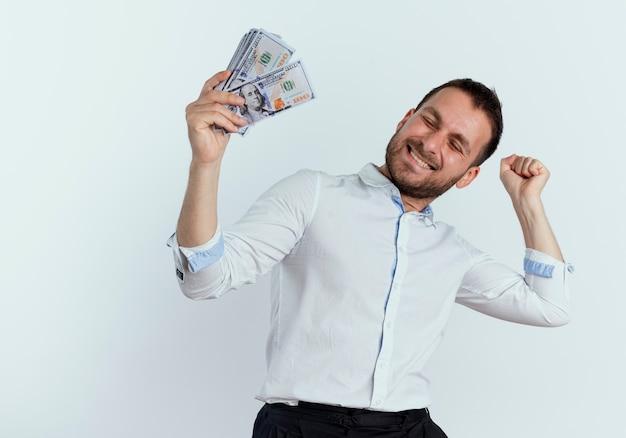 Homem bonito feliz segurando dinheiro e levanta o punho isolado na parede branca