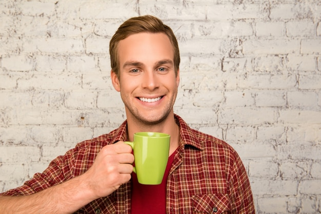 Homem bonito feliz segurando uma xícara de café quente