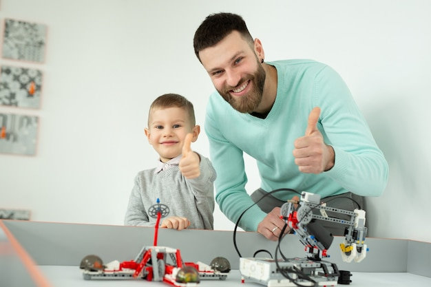 Homem bonito feliz sorrindo para a câmera com seu filho pequeno e alegre enquanto brinca com robôs lego
