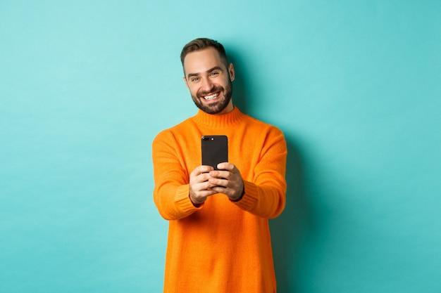 Homem bonito feliz tirando foto no celular e tirando fotos com a câmera do smartphone, em pé