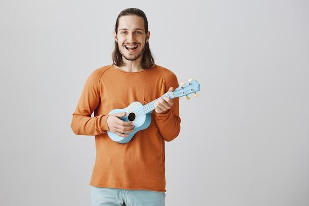 Homem bonito feliz tocando ukulele e cantando