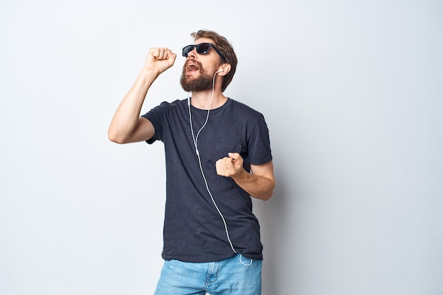 Homem bonito, fones de ouvido, óculos de sol, música, dança, diversão, isolado, fundo