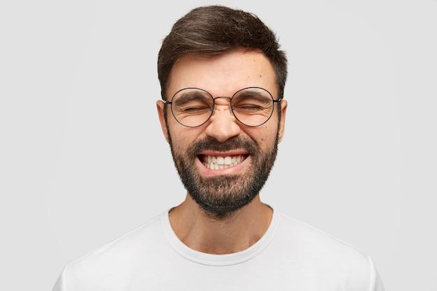 Homem bonito franze a testa e range os dentes, mantém os olhos fechados, tenta se concentrar em algo, usa camiseta casual