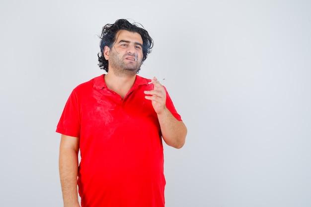 Homem bonito, fumando cigarro em t-shirt vermelha e olhando sério. vista frontal.