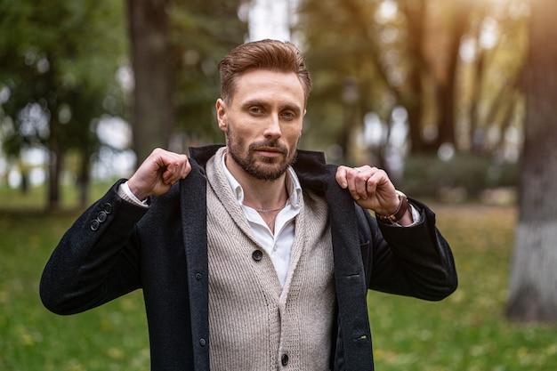Homem bonito furando as pontas de seu sobretudo em pé ao ar livre em um parque de outono, sorrindo, olhando para a frente