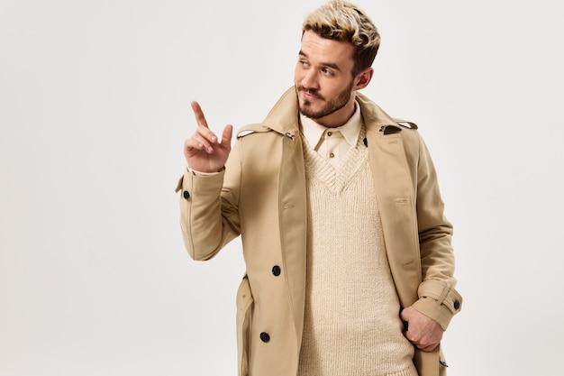 Homem bonito gesticulando com a mão bege casaco estilo moderno vista recortada