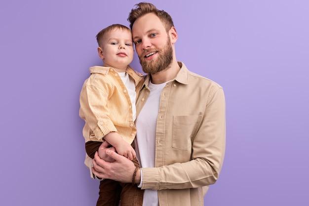 Homem bonito gosta de passar o tempo com o filho, em roupa casual, posando, jogando. família amigável isolada em fundo roxo