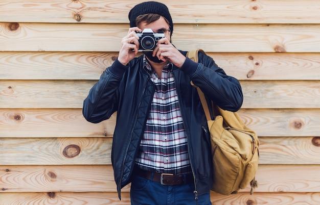 Homem bonito hippie com barba, chapéu estiloso e óculos posando com câmera retro nas mãos