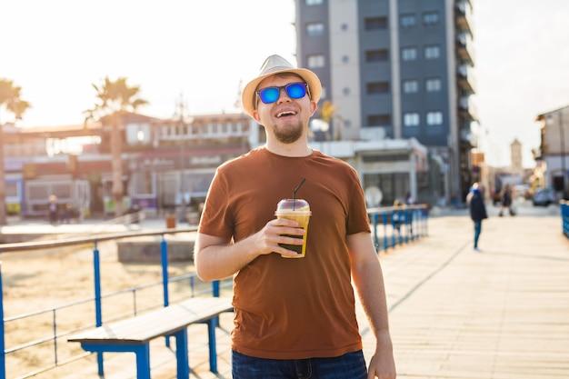 Homem bonito hipster com xícara de café de papel na rua