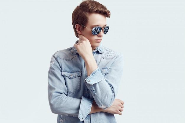 Homem bonito hipster em óculos de sol da moda vestindo jaqueta jeans