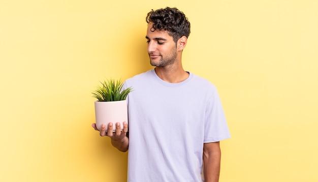Homem bonito hispânico no pensamento de vista de perfil, imaginando ou sonhando acordado. conceito de planta decorativa
