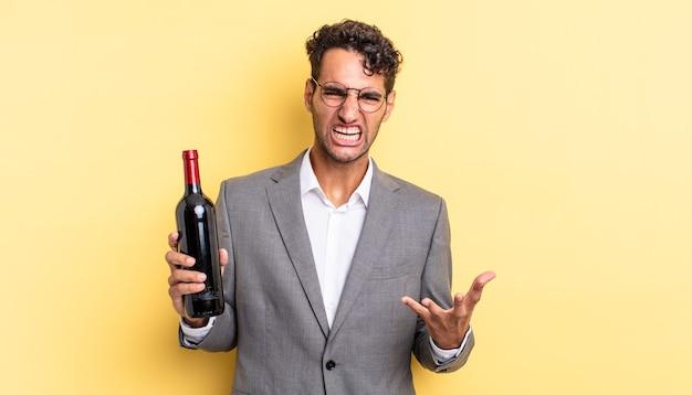 Homem bonito hispânico parecendo irritado, irritado e frustrado. conceito de garrafa de vinho