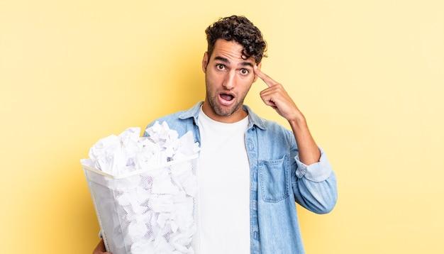 Homem bonito hispânico parecendo surpreso, percebendo um novo pensamento, ideia ou conceito. conceito de lixo de bolas de papel