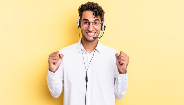 Homem bonito hispânico se sentindo chocado, rindo e comemorando o sucesso. conceito de telemarketing
