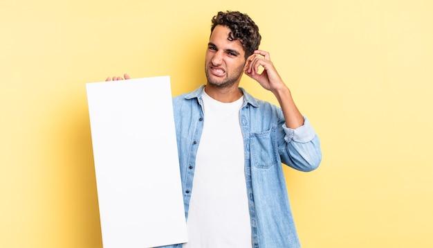 Homem bonito hispânico se sentindo confuso e perplexo, mostrando que você é louco. conceito de tela vazia