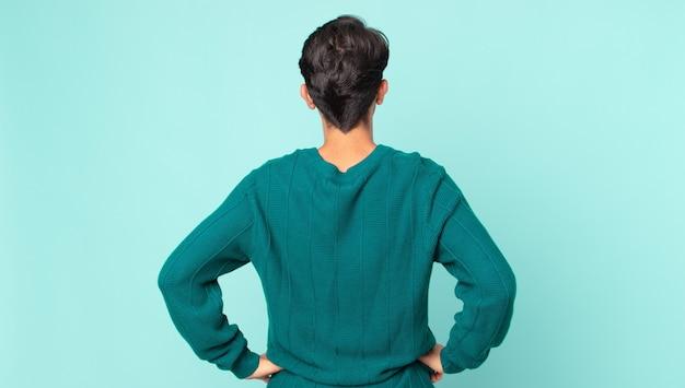 Homem bonito hispânico se sentindo confuso ou cheio ou dúvidas e perguntas, imaginando, com as mãos nos quadris, vista traseira