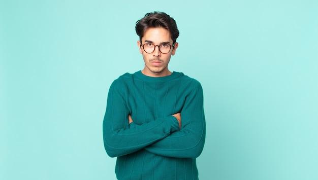 Homem bonito hispânico se sentindo descontente e desapontado, parecendo sério, irritado e com raiva de braços cruzados