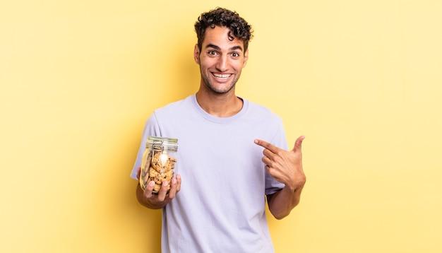 Homem bonito hispânico se sentindo feliz e apontando para si mesmo com um animado. conceito de biscoitos