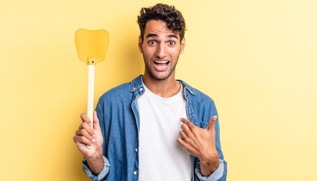 Homem bonito hispânico se sentindo feliz e apontando para si mesmo com um animado. conceito de mata moscas