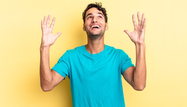 Homem bonito hispânico se sentindo feliz, pasmo, sortudo e surpreso, comemorando a vitória