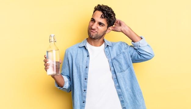 Homem bonito hispânico se sentindo perplexo e confuso, coçando a cabeça. conceito de garrafa de água