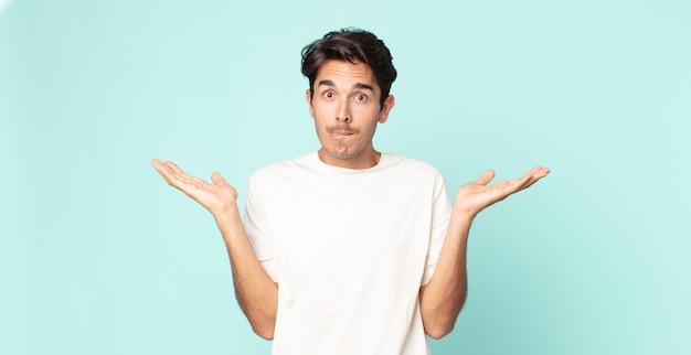 Homem bonito hispânico se sentindo perplexo e confuso, duvidando, ponderando ou escolhendo opções diferentes com expressão engraçada