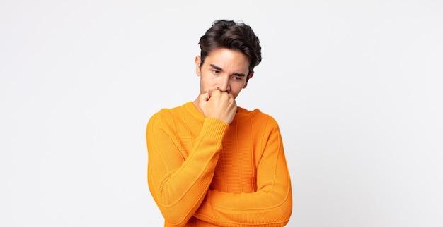 Homem bonito hispânico se sentindo sério, pensativo e preocupado, olhando de lado com a mão pressionada contra o queixo