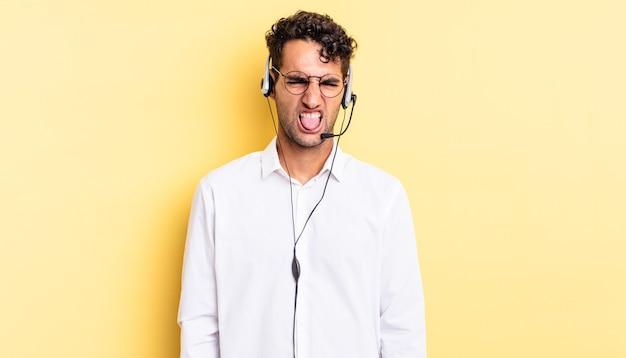 Homem bonito hispânico sentindo-se enojado e irritado e com a língua de fora. conceito de telemarketing