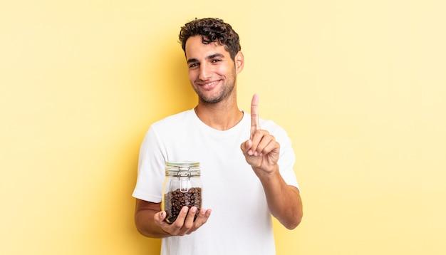 Homem bonito hispânico sorrindo com orgulho e fazendo o número um com confiança. garrafa de grãos de café