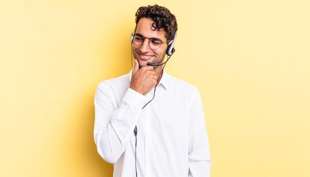 Homem bonito hispânico sorrindo com uma expressão feliz e confiante com a mão no queixo. conceito de telemarketing