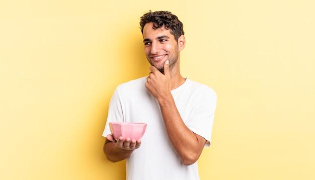 Homem bonito hispânico sorrindo com uma expressão feliz e confiante com a mão no queixo. conceito de tigela vazia
