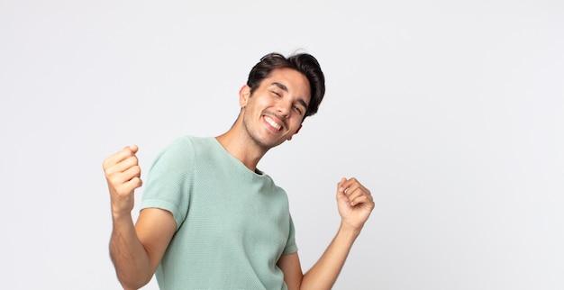 Homem bonito hispânico sorrindo, sentindo-se despreocupado, relaxado e feliz, dançando e ouvindo música, se divertindo em uma festa