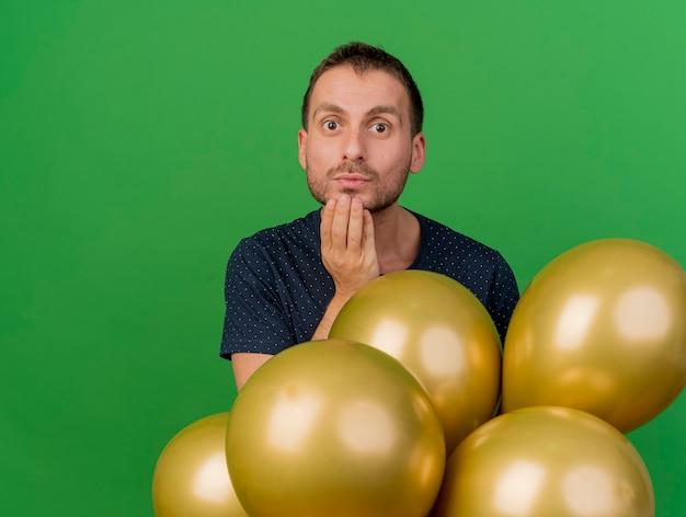 Homem bonito impressionado coloca a mão no queixo e segura balões de hélio isolados na parede verde
