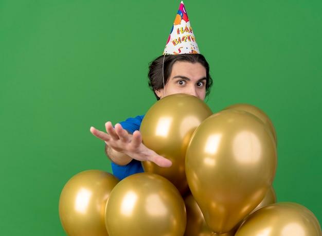 Homem bonito impressionado com boné de aniversário e balões de hélio estendendo as mãos isoladas na parede verde