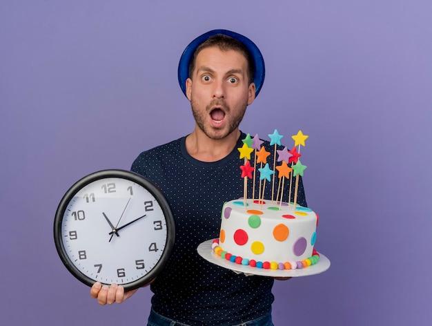 Homem bonito impressionado com chapéu azul segurando bolo de aniversário e relógio isolados na parede roxa com espaço de cópia