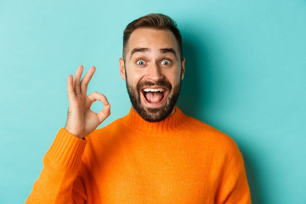 Homem bonito impressionado mostrando sinal de ok, recomendando algo bom, elogiando com gesto de ok