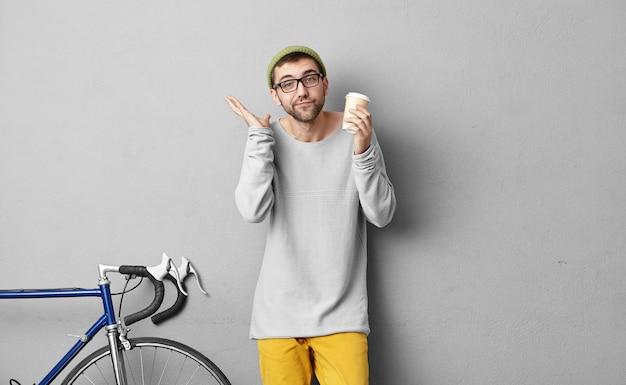 Homem bonito incerto com cerdas, mantendo o café para viagem na mão, parado na loja, escolhendo a bicicleta para si mesmo, sem saber o que escolher, encolhendo os ombros com dúvidas. escolha difícil