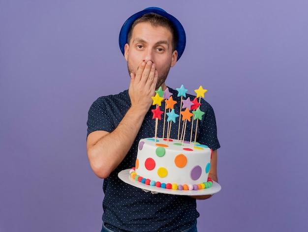 Homem bonito irritado com chapéu azul coloca a mão na boca e segura um bolo de aniversário isolado na parede roxa