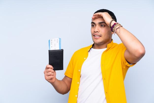 Homem bonito, isolado na parede azul em férias com bilhetes de avião e passaporte enquanto olha algo à distância