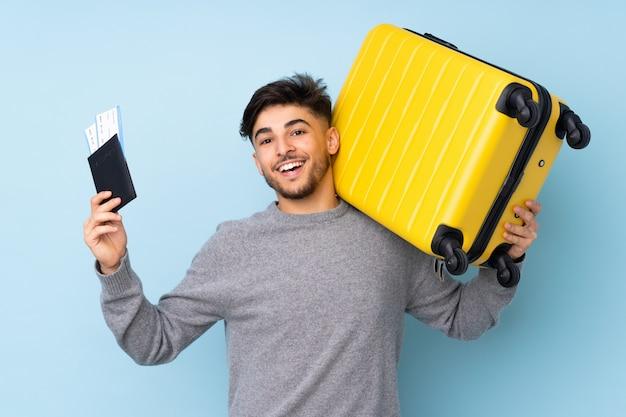 Homem bonito, isolado na parede azul em férias com mala e passaporte