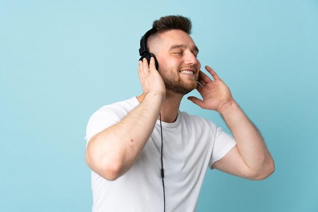 Homem bonito, isolado na parede azul, ouvir música e cantar