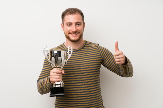 Homem bonito isolado parede branca segurando um troféu