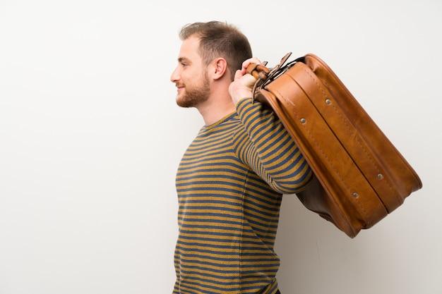 Homem bonito isolado parede branca segurando uma maleta vintage