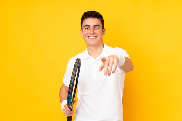Homem bonito jogador de tênis adolescente isolado em fundo amarelo, jogando tênis e apontando para a frente