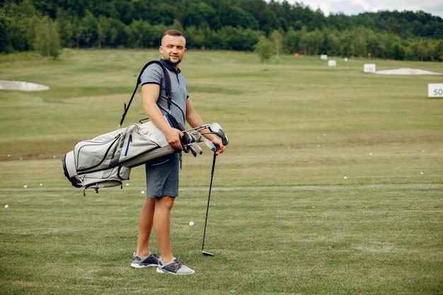 Homem bonito, jogando golfe em um campo de golfe