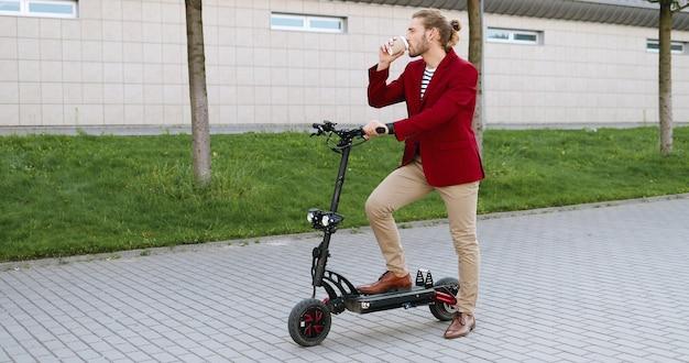 Homem bonito jovem caucasiano com jaqueta vermelha em pé na rua na scooter elétrica e bebendo café. cara elegante tomando uma bebida para ir ao ar livre. pare para descansar. lugar da cidade.