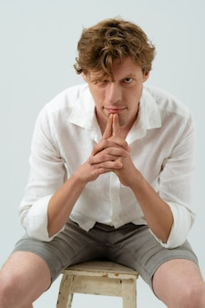 Homem bonito jovem confiante sentado na cadeira, pensativo, olhando para a câmera