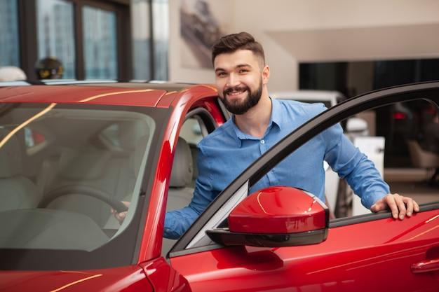 Homem bonito jovem feliz entrando no carro no salão da concessionária.