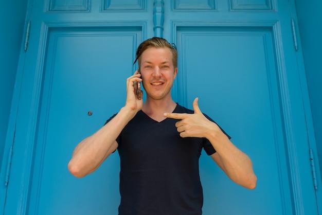 Homem bonito jovem feliz falando no celular e apontando o dedo na frente da porta azul